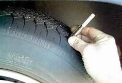 Checking tire tread depth.